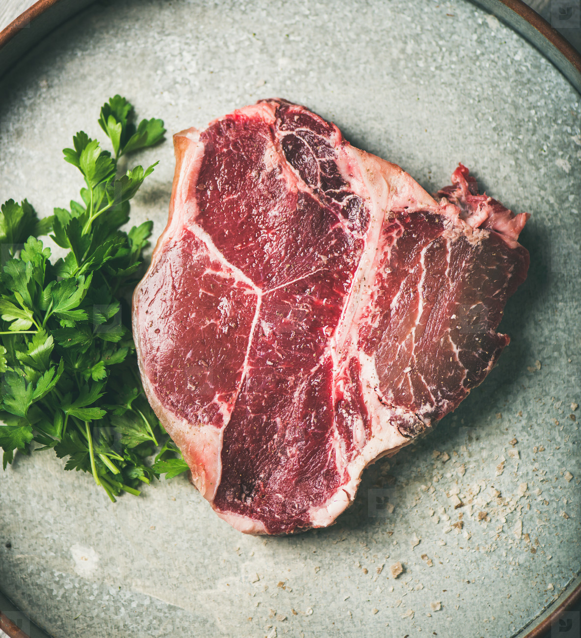 Flat lay of raw uncooked dry aged t bone prime beef steak