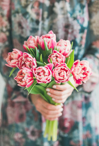 Woman in colorful dress holding bouquet of pink tulips