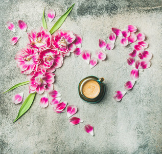 Cup of coffee pink tulip flowers and petals