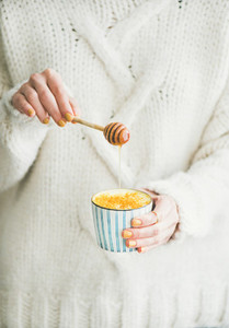 Healthy Turmeric Latte with Honey in females hands