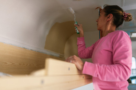 Young blonde woman painting and restoring caravan