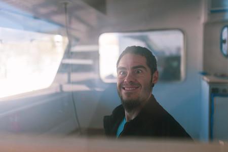 young man playing dumb inside his caravan