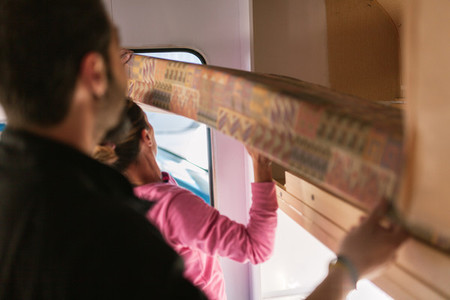 Young couple painting and restoring caravan