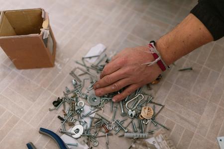 Mans hand closeup searching screws in the floor of his caravan