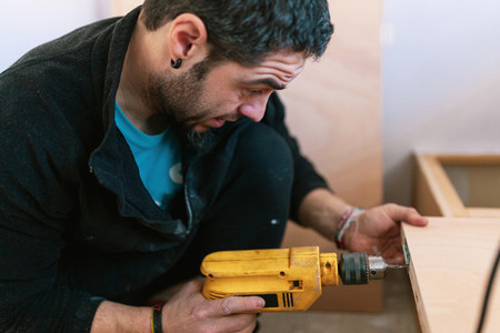 Young man with a drill restoring his old caravan