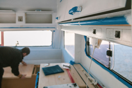 Young man restoring his old caravan from inside