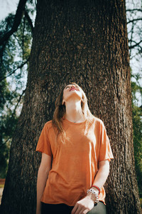 Young blonde woman supported on a tree with black jeans