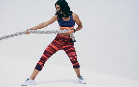 Woman in fitness wear pulling a battle rope