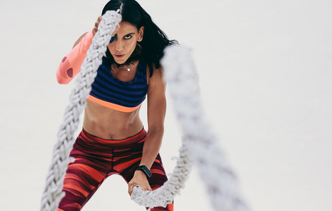 Close up of a fitness woman working out using battle ropes