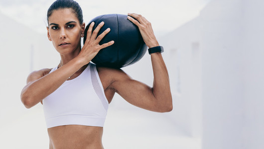 Portrait of a woman athlete training with a medicine ball