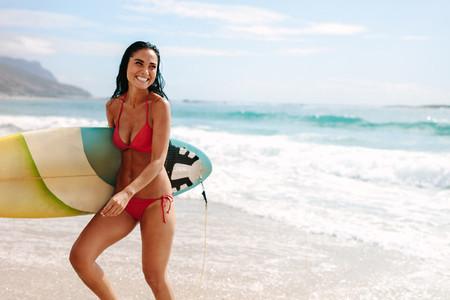 Female surfer on the sea shore
