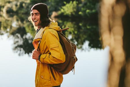 Tourist man walking beside a lake