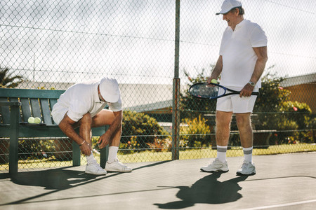 Senior men getting ready for a game of tennis