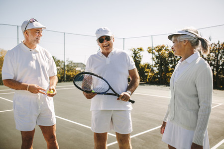 Senior men and a woman playing tennis