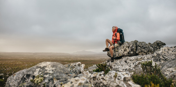 Woman hiker sitting on a hill relaxing