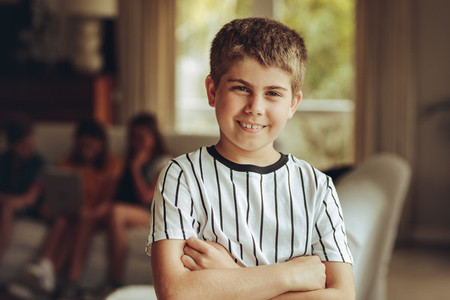 Kid standing at home with arms crossed