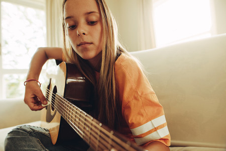 Girl practicing guitar at home