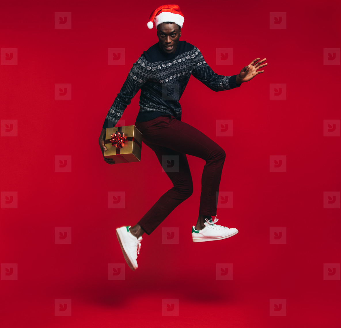 Stylish man jumping with christmas present