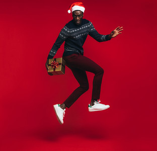 Stylish man jumping with christmas present