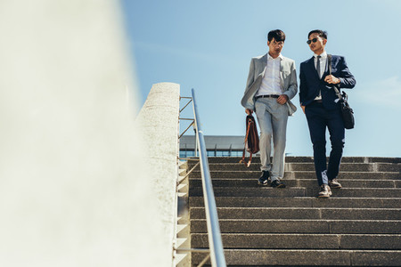 Business men talking and walking down the steps