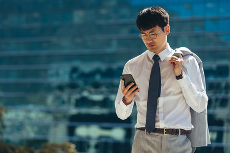 Businessman walking outdoors using his smart phone
