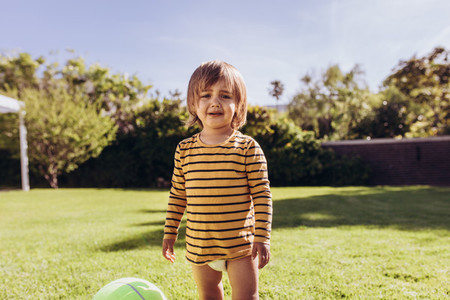 Kid standing in a park beside a ball