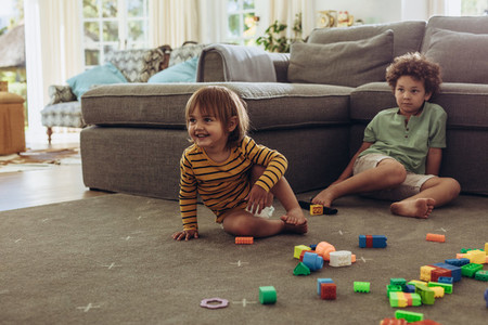 Kids playing at home sitting on floor