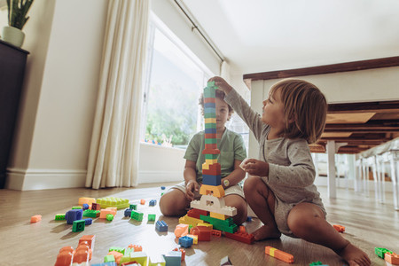 Kids playing with building blocks at home