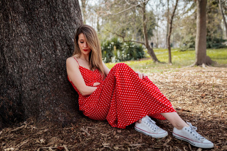 Young serious blond woman sitting near tree with red long dress
