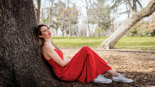 Young smile blond woman sitting near tree with red long dress