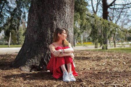 Young serious blond woman siting near tree with red long dress