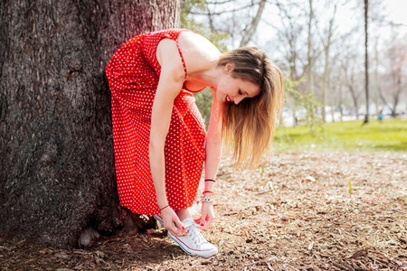 Young smiling blond woman leaning tying her sneakers whit dress