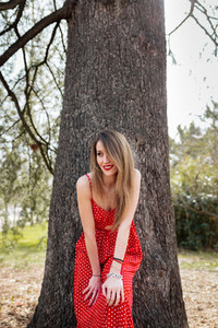 Young smiling woman with red dress leaning towards the camera