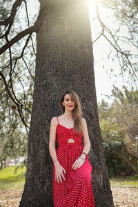Young smiling blond woman with red dress leaning against a tree