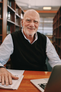 Cheerful senior man learning sitting at a library