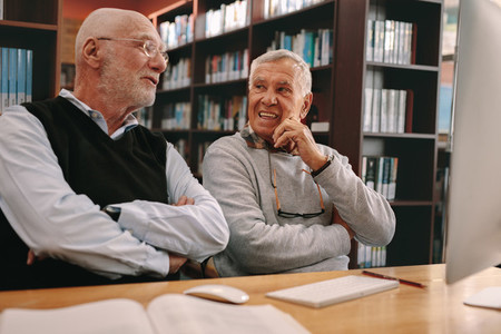Senior men sitting in a classroom and talking