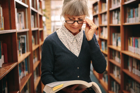 Portrait of a senior woman in eyeglasses reading a book in libra