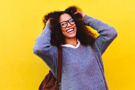 Cheerful female traveler on yellow background