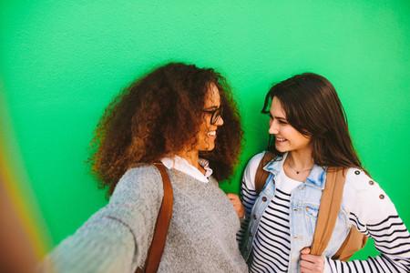 Cheerful girls travelers taking a selfie