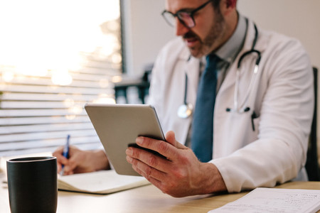 Doctor with digital tablet writing notes at his desk