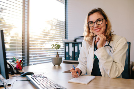 Smiling female doctor sitting her office desk
