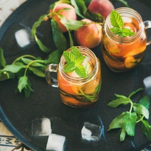 Summer refreshing cold peach ice tea in jars square crop