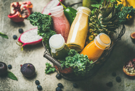 Colorful smoothies in bottles with fruits in basket selective focus