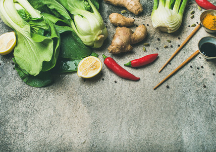 Flat lay of Asian cuisine ingredients over concrete background  copy space