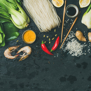 Asian cuisine ingredients over dark slate stone background square crop