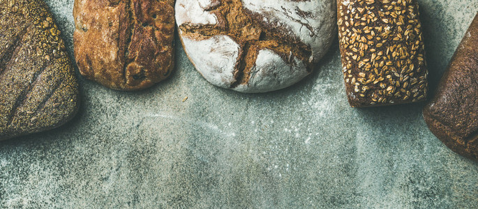 Top view of bread loaves over grey background wide composition