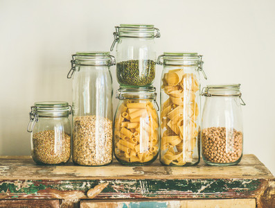 Uncooked cereals  grains  beans and pasta on rustic wooden table