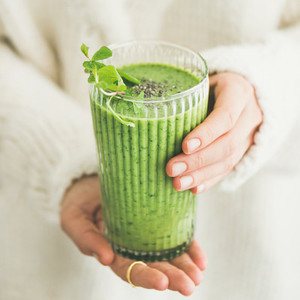 Matcha smoothie with chia seeds in female hands  square crop