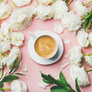 Cup of coffee and ranunculus flowers on light pink background