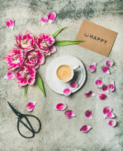 Cup of coffee surrounded with pink tulip flowers